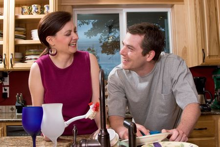 Attractive couple laughing and sharing a joke while doing the dishes in the kitchen. Horizontally framed shot. Stock Photo - 3132466