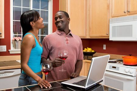 Attractive African American couple, laughing at each other, standing in a kitchen, while using a laptop.  Horizontally framed shot with the man and woman looking at each other, laughing.