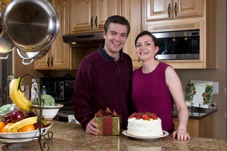 Attractive couple standing by a gift and a cake in their kitchen. Both are grinning widely and looking at the camera. Horizontally framed shot. Stock Photo - 3132506