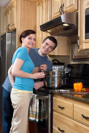 soulmate: Attractive couple standing by the stove in the kitchen and smiling at the camera. Vertically framed shot.