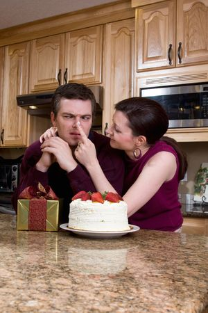 horsing around: Couple horsing around in their kitchen over gifts and cake. He is making faces while trying to stare at a spot of frosting that she put on his nose. She is looking at him and laughing. Vertically framed shot. Stock Photo