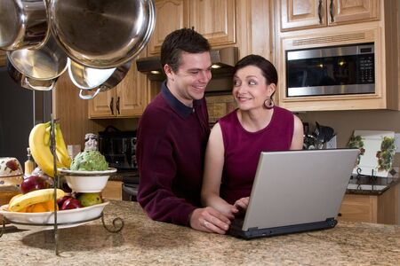 soulmate: Attractive couple standing in their kitchen and reviewing something on their laptop screen together. Both are smiling and looking at each other. Horizontally framed shot.