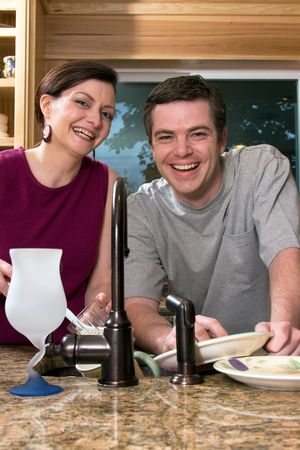 soulmate: Attractive couple smiling while doing dishes in their kitchen. Vertically framed shot.