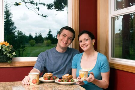 A smiling couple eating continental breakfast at home. 免版税图像