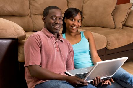 A couple sitting on the floor by a sofa with a laptop-horizontal.
