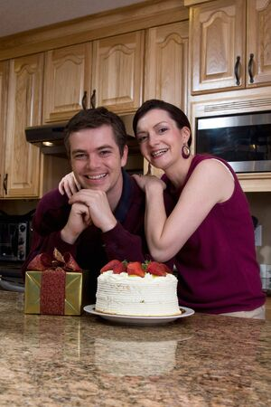 Attractive couple leaning on their kitchen counter which is covered with a cake and a present. They have a huge smile on their faces and are looking at the camera. Vertically framed shot. photo