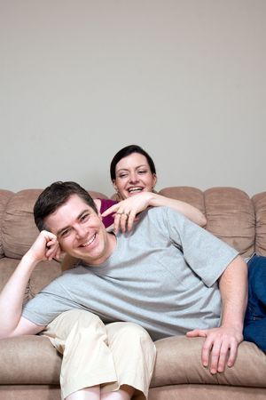 horsing around: Couple horsing around on their living room couch. He is lying in her lap and she is tickling his ear. Both are laughing at the camera. Vertically framed shot. Stock Photo