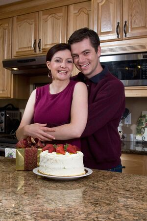 Attractive couple hugging in the kitchen by a counter covered with a cake and a present. Vertically framed shot. Pair are smiling at the camera. photo