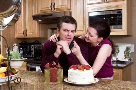 horsing around: Couple horsing around in their kitchen over gifts and cake. He is making faces while trying to stare at a spot of frosting that she put on his nose. She is looking at him and laughing. Horizontally framed shot.
