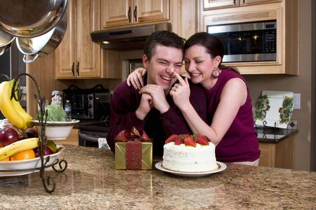 Fun-loving couple playing together in their kitchen while exchanging gifts and cake. She is brushing his nose with frosting and both are laughing. Horizontally framed shot. photo