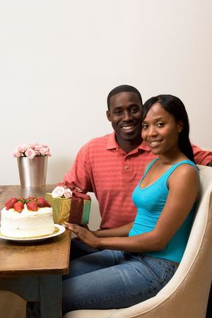 Attractive smiling couple celebrating a birthday sitting at a table.  On top of the table is a frosted cake with strawberries, a wrapped gift, and flowers.  Vertically framed side-shot with the couple looking towards the camera. Stock Photo - 3132484