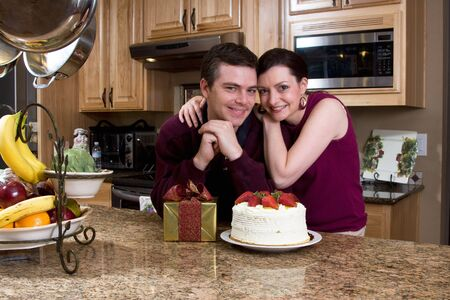 Attractive loving couple hugging and leaning on their kitchen counter which holds a cake and a gift. They are smiling at the camera. photo