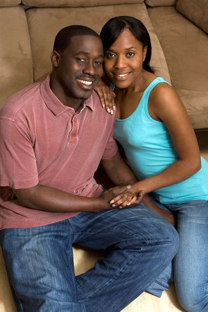 a young couple sitting on the floor by sofa holding hands. photo