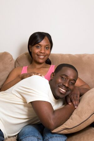 vertically: Happy, attractive couple share a couch. Both are smiling and he is lying across her lap. Vertically framed photograph.