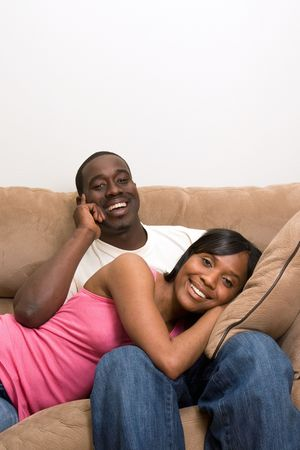 soulmate: Happy, attractive couple share a couch. He is laughing