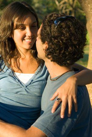 森の中で幸せな、カップル。彼女は彼女は彼女の腕彼の周り彼らとしてお互いを見て、笑顔を持っています。垂直方向にフレームの写真