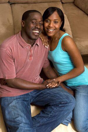 幸せな、魅力的なカップル、ソファの前の床に座っています。彼らは笑顔と手を繋いでいます。垂直方向にフレームの写真