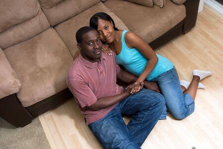 幸せな、魅力的ないくつか座っている n、ソファの前の床。彼らは手を繋いでいると笑みを浮かべてします。水平方向にフレームの写真