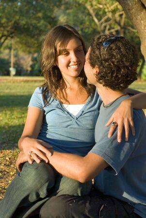 幸せなカップルは森の中で座っています。彼女は、彼らと笑顔を見て彼の膝の上に座っています。垂直方向にフレームの写真