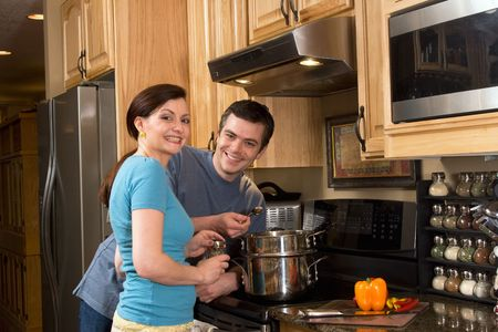 he and she: Happy, smiling couple in the kitchen near a counter, microwave, and a chopped pepper. He is about to taste the food she is cooking on the stove.  Horizontally framed photograph Stock Photo