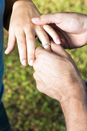 Close up of two hands. They are getting engaged as the male hand slips a ring on the female hands ring finger. Vertically framed photograph. photo