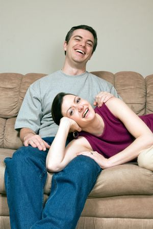 Smiling, happy couple sitting on a couch. They are laughing and he has his arm around her as she lays across his lap. Vertically framed photograph