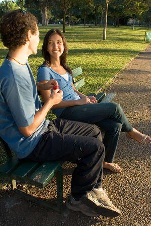 公園のベンチに座っている若いカップル。彼は彼女に赤い花を示すよう、彼らはお互いに笑っています。縦枠の写真