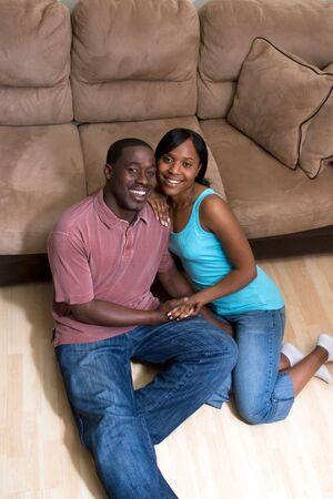 幸せな、魅力的なカップル、ソファの前の床に座っています。彼らは笑って、笑って、手を繋いでいます。垂直方向にフレームの写真