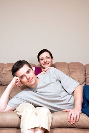 vertically: Smiling, happy couple sitting on a couch. He lays across her lap. Vertically framed photograph