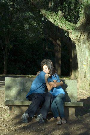 男と女のベンチに座ると抱擁します。垂直方向にフレームの写真。