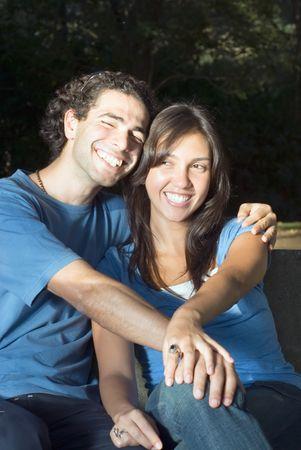 幸せな、魅力的なカップルは、公園に座ってください。彼らは笑って、お互いを受け入れてします。垂直方向にフレームの写真
