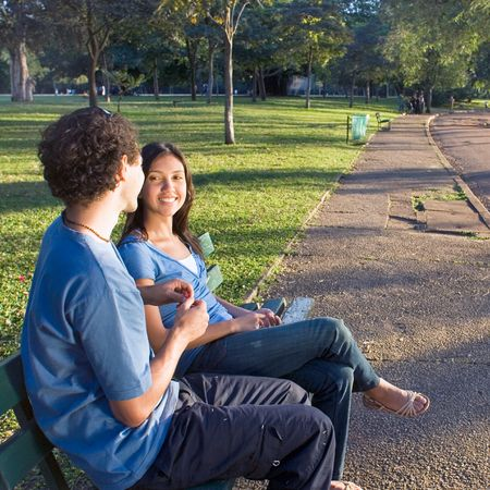 Young couple sitting on a park bench. They are smiling at each other as he shows her a red flower. Horizontally framed photograph photo