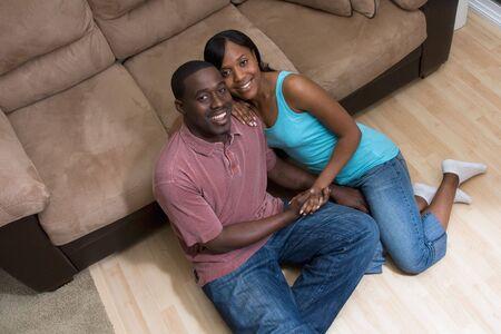 幸せな、魅力的なカップル、ソファの前の床に座っています。彼らは手を繋いでいると笑い。