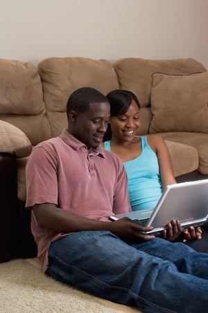 幸せな、魅力的なカップル、ソファの前の床に座っています。彼らは一緒にノート パソコンを見ています。彼女は彼の肩に彼女の腕をしています。垂直方向にフレームの写真