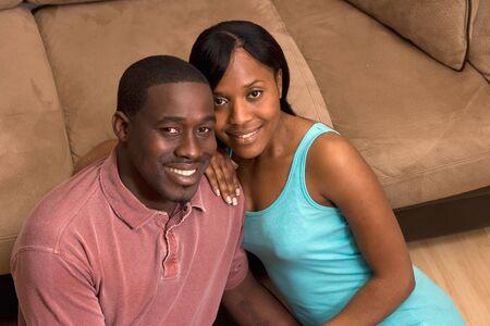 幸せな、魅力的なカップル、ソファの前の床に座っています。彼らが笑っています。クローズ アップ。水平方向にフレームの写真