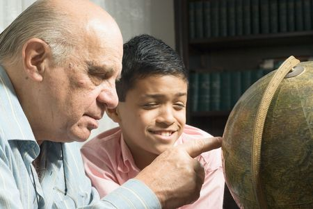 Grandfather and grandson are looking at a globe together. Grandfather is pointing at a place on the globe as the grandson  watches happily. This is a horizontally framed photo.