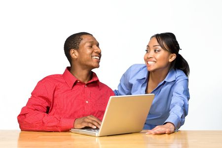 Two Teens looking at each other and smiling as he types on a Laptop Computer. Horizontally framed photograph Stock Photo - 3196676
