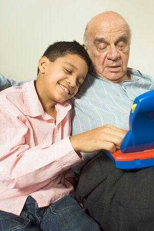 Grandson is resting his head on grandfathers shoulder as the play the game together. Grandfather watches as grandson plays. This is vertically framed. Stock Photo - 3196796