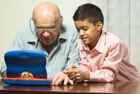 Grandfather and Grandson are seated at a table looking at a blue toy computer. Horizontally framed photograph.