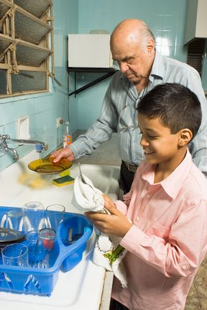Grandfather and grandson are washing the dishes together. Grandfather washes a plate under the sink as grandson happily wipes down a utensil. This is a vertically framed photo.