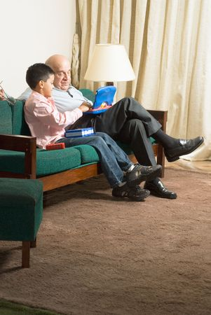 Grandfather and Grandson are seated on green couch looking at a blue laptop computer together. Vertically framed photograph. photo