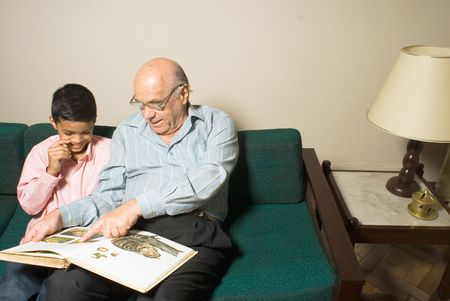 grandfather and grandson sitting on the couch while the grandfather teaches his how to read. The grandfather is pointing at the book and the grandson is smiling. This is horizontally framed.