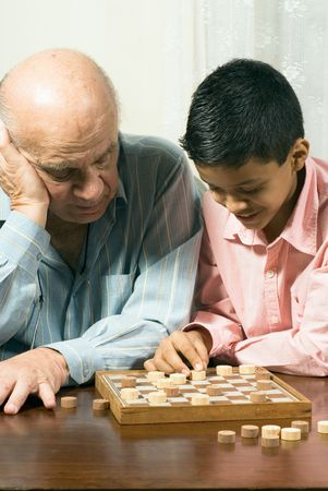 Grandfather and grandson are sitting at the table playing checkers. Grandfather watches closely as grandson moves a piece on the board. This is a vertically framed photo. Stock Photo