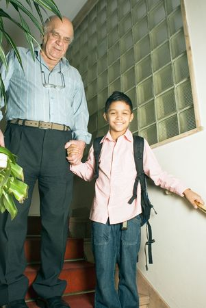 Grandfather and grandson are standing in the stairwell holding hands. Grandson is smiling with his backpack on as grandfather holds his hand. This is a vertically framed photo. photo