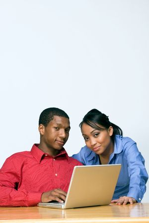 Two Teens looking serious as they stare ahead and he holds a Laptop Computer. Vertically framed photograph Stock Photo - 3196625