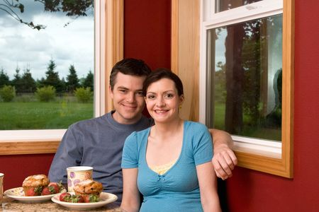 A smiling couple having breakfast by a large window at home.