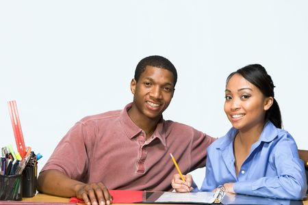 Two Teens are are seated at a desk taking notes and smiling. There are pencils, folders, and paper on the desk. Horizontally framed photgraph photo