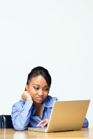 Teen girl looking bored types on a laptop computer as she sits at a desk. Horizontally framed photograph photo