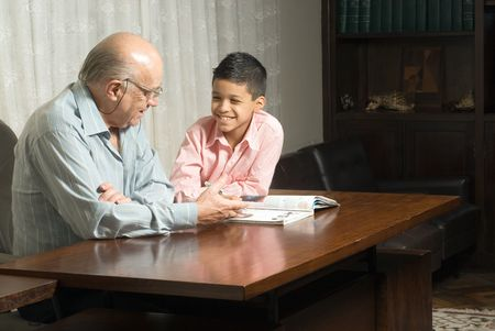 Grandfather and grandson are sitting at the table reading a book. Grandfather smiles as he reads the book to his grateful grandson. This is a horizontally framed photo. Stock Photo