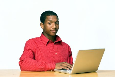 Teen boy types on a laptop computer as he sits at a desk and looks serious. Horizontally framed photograph photo